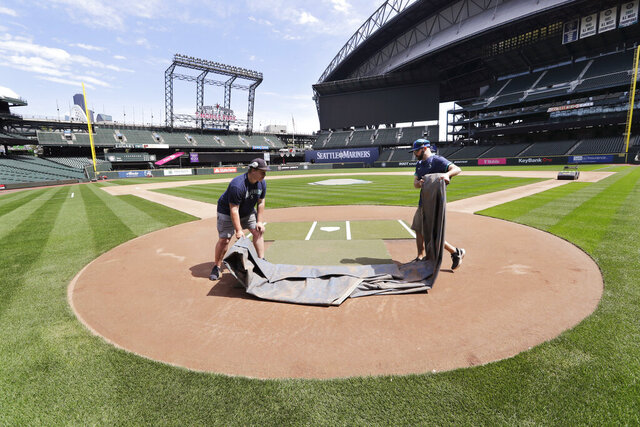 Grounds crew workers Jacob Weiderstrom, left, and Marcus Gignac pull a tarp off home plate as they continue to keep the Seattle Mariners' field in playing shape as the ballpark goes into its seventh week without baseball played because of the coronavirus outbreak Monday, May 11, 2020, in Seattle. A person familiar with the decision tells The Associated Press that Major League Baseball owners have given the go-ahead to making a proposal to the players' union that could lead to the coronavirus-delayed season starting around the Fourth of July weekend in ballparks without fans. (AP Photo/Elaine Thompson)