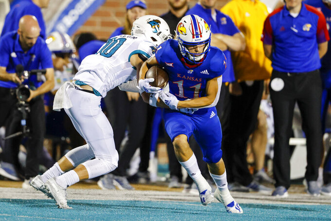 Kansas wide receiver Luke Grimm (11) breaks away from Coastal Carolina safety Alex Spillum after a catch during the first half of an NCAA college football game in Conway, S.C., Friday, Sept. 10, 2021. (AP Photo/Nell Redmond)