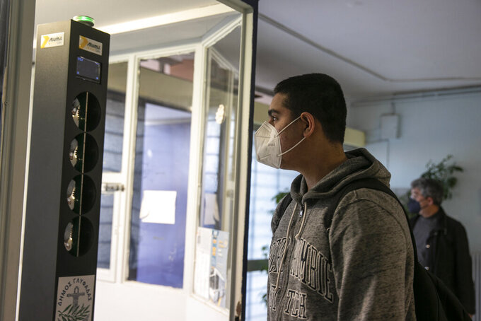 A high school student has his body temperature checked as he enters a school at Glyfada suburb, west of Athens, Monday, April 12, 2021. Home tests have been distributed to teachers and students aged 16-18, as authorities reopened high schools for students in the final three grades on Monday. (AP Photo/Yorgos Karahalis)