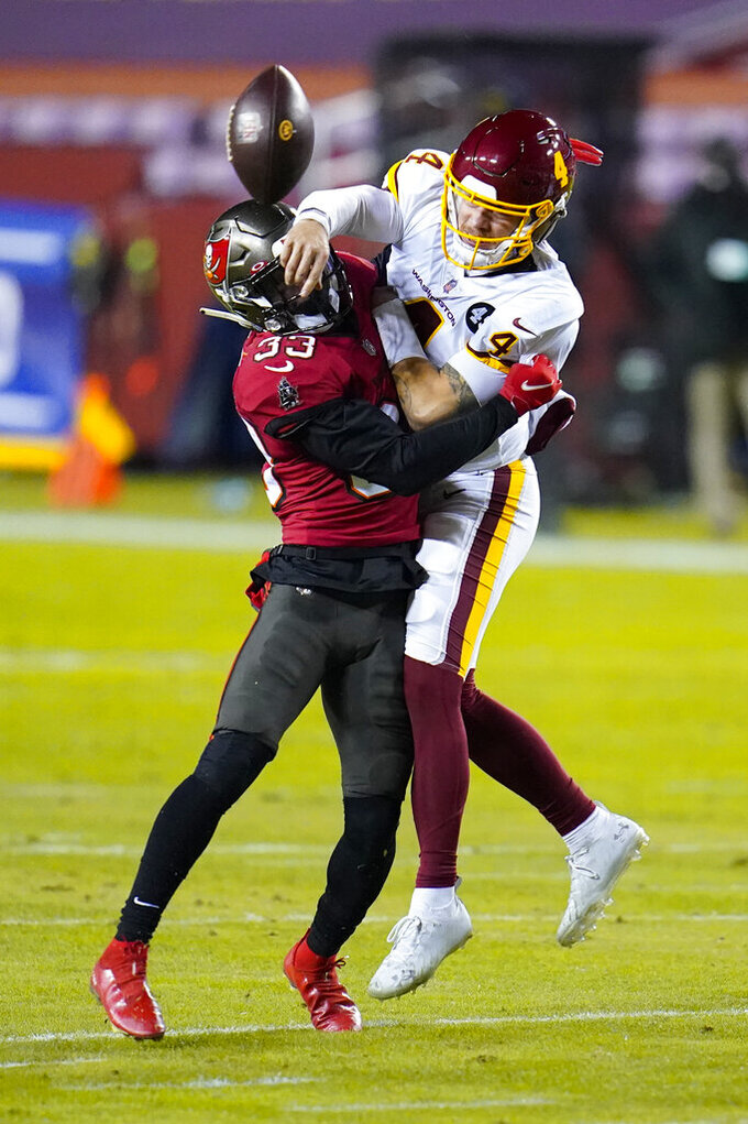 Washington Football Team quarterback Taylor Heinicke (4) is hit by Tampa Bay Buccaneers free safety Jordan Whitehead (33) during the first half of an NFL wild-card playoff football game, Saturday, Jan. 9, 2021, in Landover, Md. (AP Photo/Julio Cortez)
