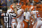 Clemson quarterback Trevor Lawrence is congratulated by teammates after he ran into the end zone for a score against Syracuse during the first half of an NCAA college football game Saturday, Sept. 14, 2019, in Syracuse, N.Y. (AP Photo/Steve Jacobs)