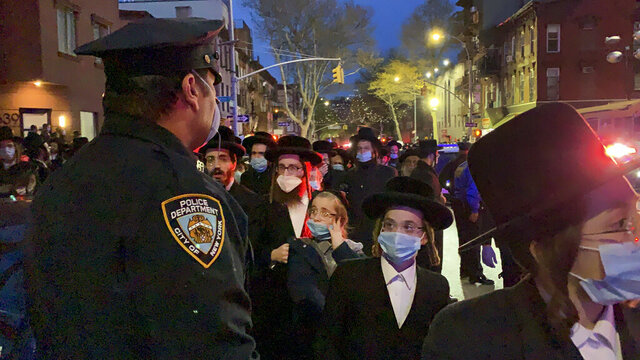 A new York City police officer keeps watch as hundreds of mourners gather in the Brooklyn borough of New York, Tuesday, April 28, 2020, to observe a funeral for Rabbi Chaim Mertz, a Hasidic Orthodox leader whose death was reportedly tied to the coronavirus. The stress of the coronavirus' toll on New York City's Orthodox Jews was brought to the fore on Wednesday after Mayor Bill de Blasio chastised