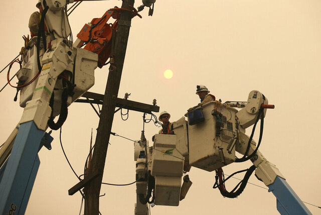 FILE - In this Nov. 9, 2018 file photo, Pacific Gas & Electric crews work to restore power lines in Paradise, Calif.  California Gov. Gavin Newsom has rejected Friday, Dec. 13, 2019, a bankruptcy reorganization plan that Pacific Gas and Electric reached just last week with thousands of wildfire victims. Newsom says in a five-page letter to PG&E CEO William D. Johnson that the plan's most important elements are providing safe and reliable power to its customers. (AP Photo/Rich Pedroncelli, File)