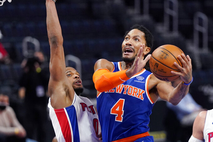 New York Knicks guard Derrick Rose (4) attempts a layup as Detroit Pistons guard Dennis Smith Jr. (0) defends during the first half of an NBA basketball game, Sunday, Feb. 28, 2021, in Detroit. (AP Photo/Carlos Osorio)
