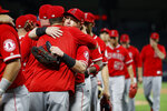 Los Angeles Angels' Kole Calhoun, center, hugs a teammate after the Angels' 9-4 win against the Texas Rangers in a baseball game in Arlington, Texas, Tuesday, July 2, 2019. (AP Photo/Tony Gutierrez)
