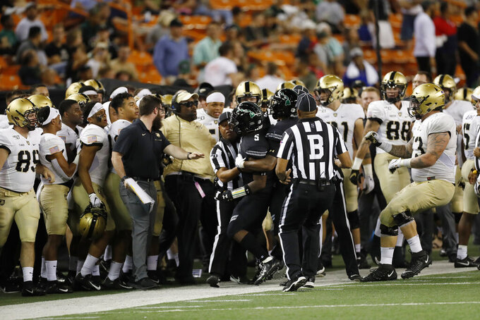 After shoving Army quarterback Christian Anderson (13) gets out of bounds, Hawaii defensive back Khoury Bethley (5) gets pulled out of the Army bench area after a fracas during the second half of an NCAA college football game Saturday, Nov. 30, 2019 in Honolulu. (AP Photo/Marco Garcia)