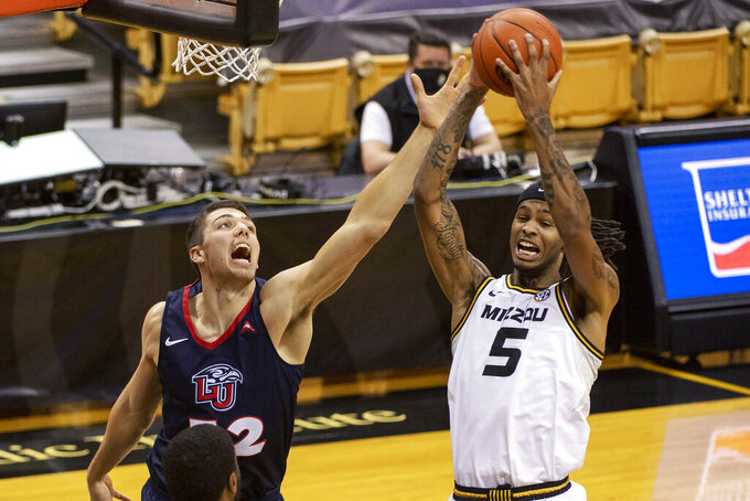 Missouri's Mitchell Smith, right, pulls down a rebound next to Liberty's Blake Preston during the first half of an NCAA college basketball game Wednesday, Dec. 9, 2020, in Columbia, Mo. (AP Photo/L.G. Patterson)