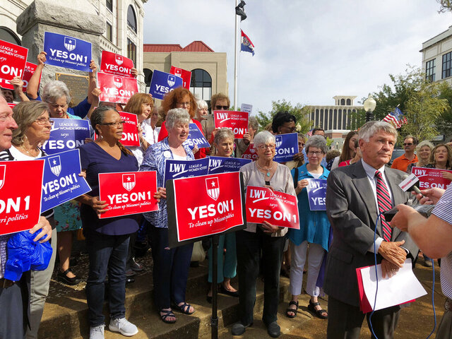 FILE - In this Aug. 31, 2018 file photo, supporters of Missouri's redistricting ballot measure hold signs behind former state Sen. Bob Johnson as he serves as their spokesman during a press conference outside the Cole County Courthouse in Jefferson City, Mo. With the U.S. census approaching, some state lawmakers are attempting to alter voter-approved measures that were intended to reduce partisan gamesmanship when drawing new districts for the U.S. House and state legislatures. (AP Photo/David A. Lieb, File)