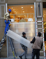 Workers set up protection on shop windows on the Champs-Elysees avenue, Friday, Dec. 7, 2018 in Paris. Many shop owners across the French capital are getting ready for the violence, setting up walls with carton boards to protect their windows. (AP Photo/Francois Mori)