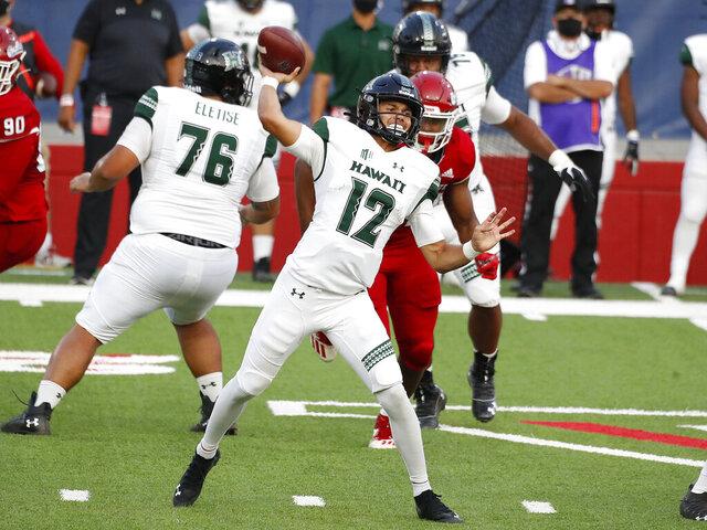 Hawaii quarterback Chevan Cordeiro passes downfield against Fresno State quarterback during the first half of an NCAA college football game in Fresno, Calif., Saturday, Oct. 24, 2020. (AP Photo/Gary Kazanjian)