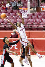 Alabama forward/guard Herbert Jones (1) chases a rebound over Georgia guard Justin Kier (5) during the second half of an NCAA college basketball game on Saturday, Feb. 13, 2021, in Tuscaloosa, Ala. (AP Photo/Vasha Hunt)