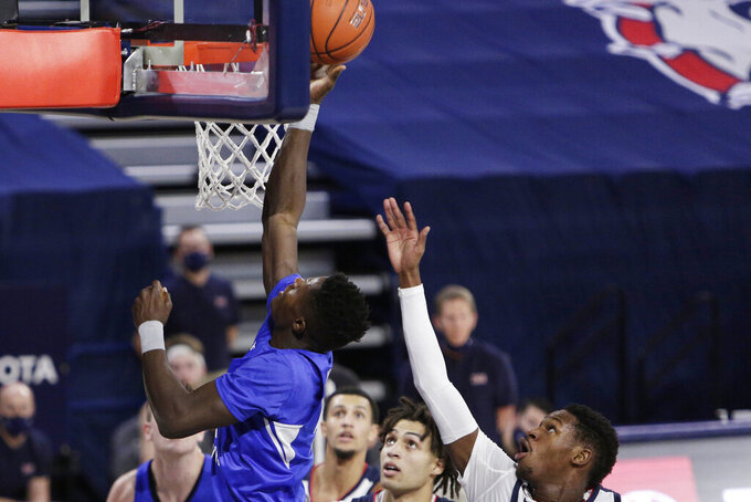 BYU forward Gideon George, left, shoots in front of Gonzaga guard Joel Ayayi, right, during the first half of an NCAA college basketball game in Spokane, Wash., Thursday, Jan. 7, 2021. (AP Photo/Young Kwak)