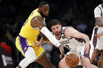 Los Angeles Lakers' LeBron James, left, strips the ball from Brooklyn Nets' Joe Harris during the first half of an NBA basketball game Tuesday, March 10, 2020, in Los Angeles. (AP Photo/Marcio Jose Sanchez)