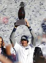 Nevada head coach Jay Norvell holds up the trophy after defeating Arkansas State in an NCAA college football bowl game, Saturday, Dec. 29, 2018, in Tucson, AZ. (AP Photo/Rick Scuteri)
