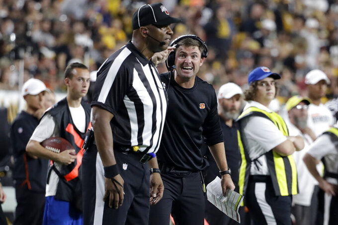 Cincinnati Bengals head coach Zac Taylor, right center, questions a call with Down Judge Phil McKinnely during the first half of an NFL football game against the Pittsburgh Steelers in Pittsburgh, Monday, Sept. 30, 2019. (AP Photo/Don Wright)