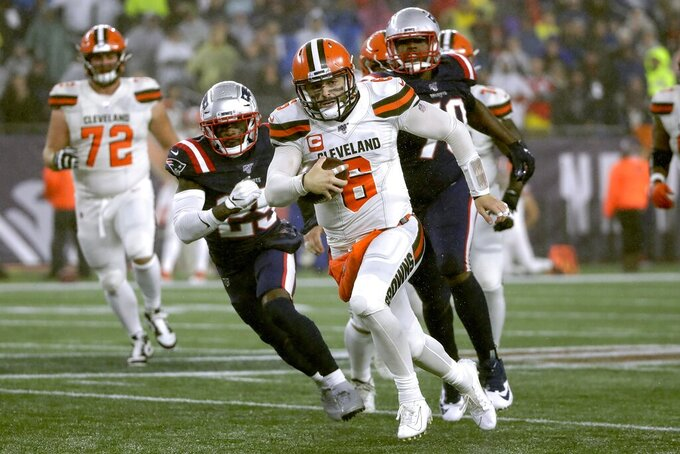 Cleveland Browns quarterback Baker Mayfield, center, runs from New England Patriots defensive back Terrence Brooks, left, and defensive tackle Adam Butler, right, in the second half of an NFL football game, Sunday, Oct. 27, 2019, in Foxborough, Mass. (AP Photo/Elise Amendola)