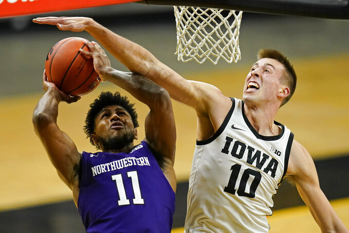 Northwestern guard Anthony Gaines (11) is fouled by Iowa guard Joe Wieskamp (10) during the first half of an NCAA college basketball game, Tuesday, Dec. 29, 2020, in Iowa City, Iowa. (AP Photo/Charlie Neibergall)