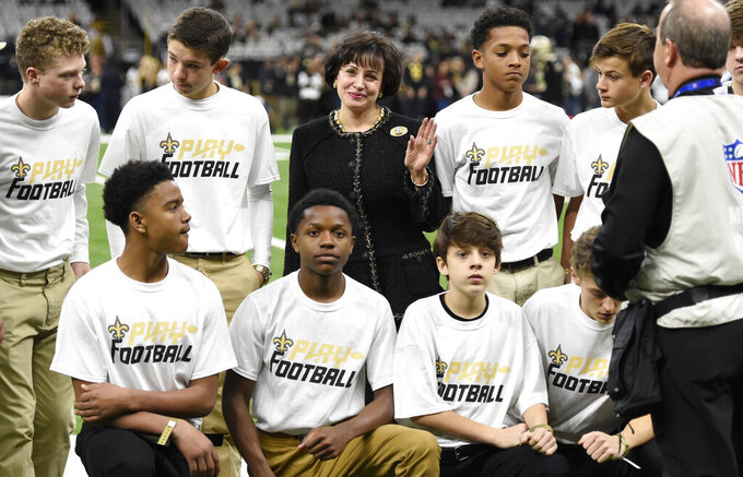 New Orleans Saints owner Gayle Benson poses with kids from the NFL Play Football initiative before an NFL divisional playoff football game against the Philadelphia Eagles in New Orleans, Sunday, Jan. 13, 2019. (AP Photo/Bill Feig)