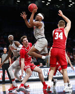 New Mexico guard JJ Caldwell (11) shoots as Wisconsin forward Nate Reuvers (35) and guard Brad Davison (34) watch from the floor in the second half of an NCAA college basketball game in the Legends Classic, Tuesday, Nov. 26, 2019, in New York. New Mexico defeated Wisconsin 59-50. (AP Photo/Kathy Willens)