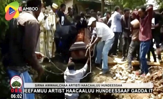 In this image taken from OBN video, the coffin carrying Ethiopia singer Hachalu Hundessa is lowered into the ground during the funeral in Ambo, Ethiopia, Thursday July 2, 2020. More than 80 people have been killed in unrest in Ethiopia after the popular singer Hachalu Hundessa was shot dead this week. He was buried Thursday amid tight security. He had been a prominent voice in anti-government protests that led to a change in leadership in 2018. (OBN via AP)