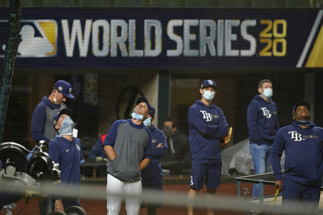 Tampa Bay Rays manager Kevin Cash, center with face mask down, watchers over a practice at Globe Life Field as the team prepares for the baseball World Series against the Los Angeles Dodgers, in Arlington, Texas, Wednesday, Oct. 14, 2020. (AP Photo/Eric Gay)