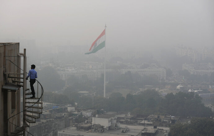 FILE - In this Nov. 1, 2019, file photo, an Indian walks up to the stairs as Delhi's sky line is seen enveloped in smog and dust in New Delhi, India. Authorities in New Delhi launched an anti-pollution campaign on Monday in an attempt to curb air pollution levels ahead of winter, when the capital is regularly covered in toxic haze, and warned that filthy air could make the coronavirus pandemic more dangerous. (AP Photo/Manish Swarup, File)