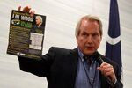 Pro-Trump attorney Lin Wood, a candidate for chairman of the South Carolina Republican Party, holds up a flyer funded by his opponent, current Chairman Drew McKissick, as he speaks to attendees of the Richland County GOP convention on Friday, April 30, 2021, in Columbia, S.C. (AP Photo/Meg Kinnard)