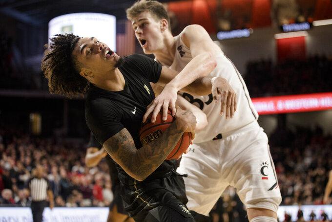 Central Florida guard Brandon Mahan (13) is fouled by Cincinnati center Chris Vogt (33) in overtime of an NCAA college basketball game Wednesday, Feb. 19, 2020, in Cincinnati. (Albert Cesare/The Cincinnati Enquirer via AP)