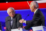 Democratic presidential candidate Sen. Bernie Sanders, I-Vt., listens as former Vice President Joe Biden, right, speaks during a Democratic presidential primary debate hosted by CNN/New York Times at Otterbein University, Tuesday, Oct. 15, 2019, in Westerville, Ohio. (AP Photo/John Minchillo)