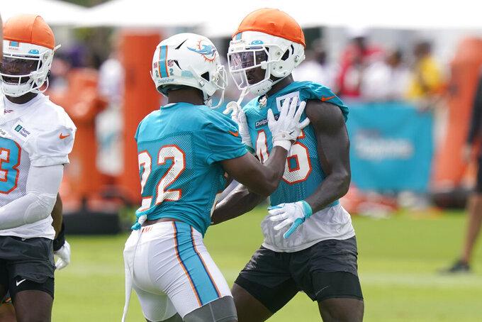 Miami Dolphins safety Jevon Holland holds cornerback Tino Ellis (46) during an NFL football practice, Monday, Aug. 2, 2021, in Miami Gardens, Fla. (AP Photo/Marta Lavandier)