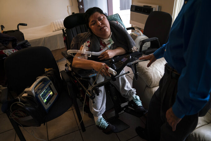 A blood oxygen monitor is attached to Socorro Franco-Martinez, who has muscular dystrophy, after she received the second dose of the Pfizer COVID-19 vaccine at her apartment, Wednesday, May 12, 2021, in Torrance, Calif. Teamed up with the Torrance Fire Department, Torrance Memorial Medical Center started inoculating people at home in March, identifying people through a city hotline, county health department, senior centers and doctor's offices, said Mei Tsai, the pharmacist who coordinates the program. (AP Photo/Jae C. Hong)