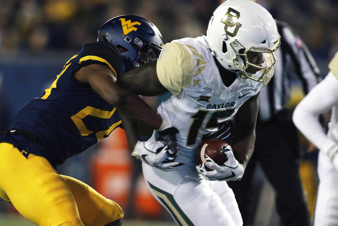 Baylor wide receiver Denzel Mims (15) is tackled by West Virginia cornerback Hakeem Bailey (24) during the second half of an NCAA college football game, Thursday, Oct. 25, 2018, in Morgantown, W.Va. (AP Photo/Raymond Thompson)