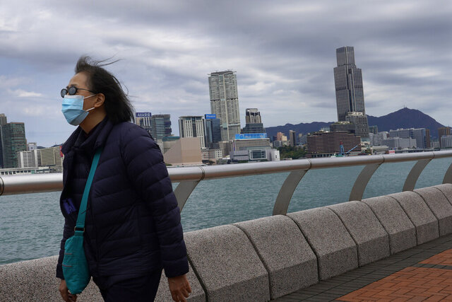 A woman wearing a face mask walks at the waterfront against the Victoria Habour in Hong Kong Sunday, Feb. 16, 2020. COVID-19 viral illness has sickened tens of thousands of people in China since December. (AP Photo/Vincent Yu)