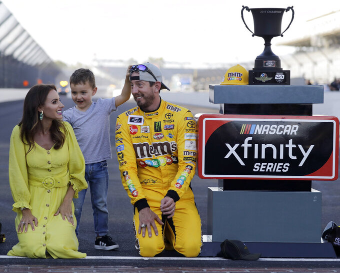 FILE - In this Sept. 7, 2019, file photo, NASCAR Xfinity Series driver Kyle Busch, right, celebrates with his wife, Samantha, and son, Brexton, after winning a NASCAR Xfinity auto race at Indianapolis Motor Speedway in Indianapolis. The Busch family hobby came full circle at Las Vegas Motor Speedway, where Kurt Busch finally won for the first time in his career Sunday, Sept. 27, 2020. The victory came about 24 hours after his nephew, Brexton, won his first race at a track in North Carolina. The 5-year-old son of reigning Cup champion Kyle is being developed by Tom Busch, who molded his own two sons into NASCAR champions. (AP Photo/Darron Cummings, File)
