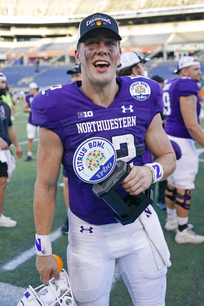 Northwestern quarterback Peyton Ramsey holds his MVP trophy after winning the Citrus Bowl NCAA college football game against Auburn, Friday, Jan. 1, 2021, in Orlando, Fla. Ramsey threw three touchdown passes and ran for a score. Northwestern defeated Auburn 35-19. (AP Photo/John Raoux)