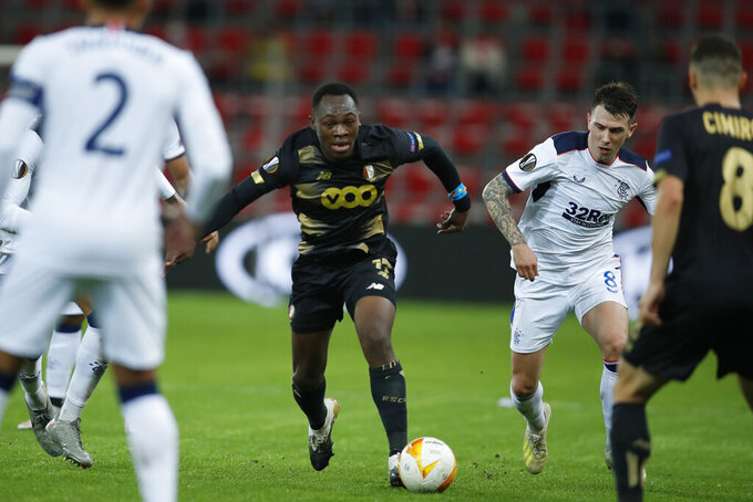 Liege's Jackson Muleka, center, is challenged by Rangers' Ryan Jack, second right, during a Europa League Group D soccer match between Standard Liege and Rangers at the Maurice Dufrasne stadium in Liege, Belgium, Thursday, Oct. 22, 2020. (AP Photo/Francisco Seco)