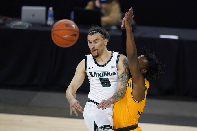Cleveland State's Tre Gomillion (5) makes a pass against Oakland's Rashad Williams (1) during the first half of an NCAA college basketball game in the men's Horizon League conference tournament championship game, Tuesday, March 9, 2021, in Indianapolis. (AP Photo/Darron Cummings)
