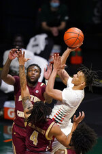 Miami guard Isaiah Wong, right, shoots against Boston College guards Jay Heath, rear and Makai Ashton-Langford (4) during the second half of an NCAA college basketball game Friday, March 5, 2021, in Coral Gables, Fla. (AP Photo/Wilfredo Lee)