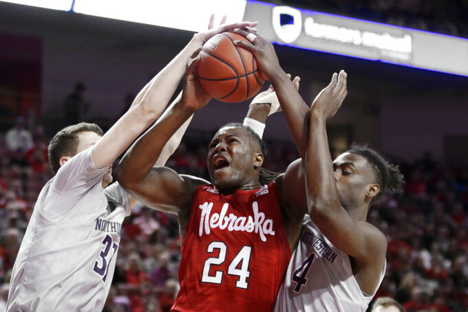 Nebraska's Yvan Ouedraogo (24) is fouled as he goes to the basket against Northwestern's Robbie Beran (31) and Jared Jonesc(4), during the first half of an NCAA college basketball game in Lincoln, Neb., Sunday, March 1, 2020. (AP Photo/Nati Harnik)