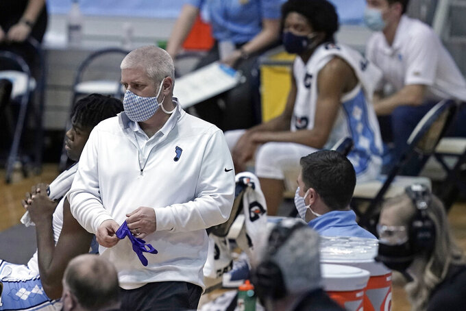 North Carolina trainer Doug Halverson works the bench area during the team's NCAA college basketball game against Syracuse in Chapel Hill, N.C., Tuesday, Jan. 12, 2021. The coronavirus pandemic has added another constantly shifting layer to what they do. The last 10 months have turned into a complicated juggling act of tending to athletes' day-to-day needs while dealing with the intricacies that come with trying to play sports and keeping everyone safe — themselves included — in a pandemic. (AP Photo/Gerry Broome)