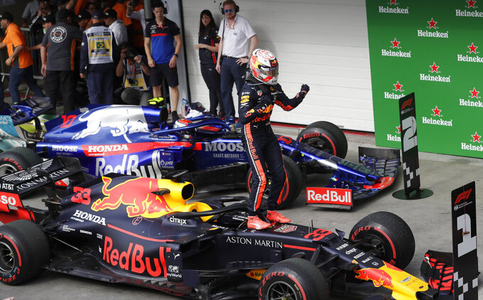 Red Bull driver Max Verstappen, of the Netherlands, celebrates atop his car after winning the Brazilian Formula One Grand Prix at the Interlagos race track in Sao Paulo, Brazil, Sunday, Nov. 17, 2019. (AP Photo/Silvia Izquierdo)