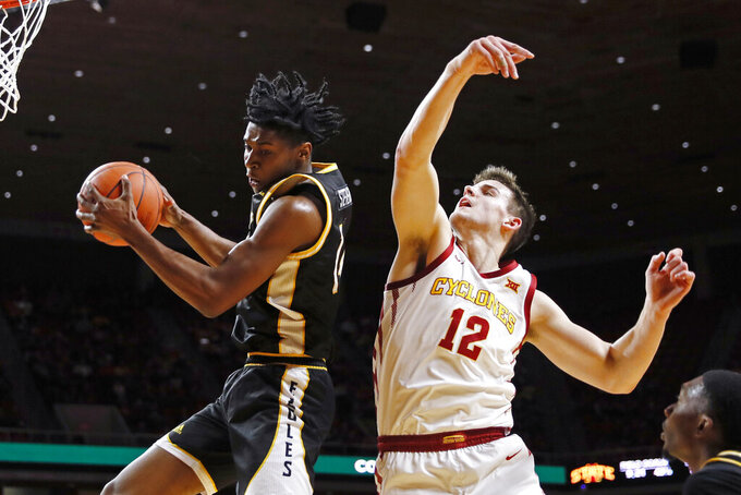 Southern Mississippi forward Tyler Stevenson grabs a rebound in front of Iowa State forward Michael Jacobson (12) during the first half of an NCAA college basketball game, Tuesday, Nov. 19, 2019, in Ames, Iowa. (AP Photo/Charlie Neibergall)