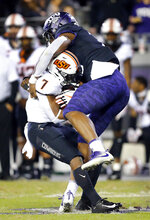 TCU defensive end Ben Banogu (15) brings down Oklahoma State running back LD Brown (7) during the fourth quarter of an NCAA college football game Saturday, Nov. 24, 2018, in Fort Worth, Texas. TCU won 31-24. (Tom Fox/The Dallas Morning News via AP)