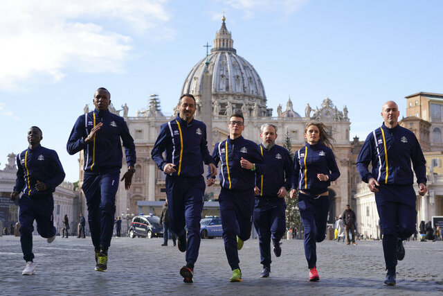 FILE - In this Jan. 10, 2019, file photo, members of the Vatican Athletics sports team run for the media in front of St. Peter's basilica, at the Vatican. The Vatican launched the official track team, complete with Swiss Guards, priests and nuns. The team is part of the Holy See's effort to use sports as an instrument for dialogue, peace and solidarity.  (AP Photo/Andrew Medichini, File)