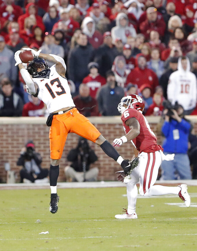 Oklahoma State wide receiver Tyron Johnson (13) makes a catch over Oklahoma cornerback Tre Brown (6) in the second half of an NCAA college football game in Norman, Okla., Saturday, Nov. 10, 2018. Oklahoma won 48-47. (AP Photo/Alonzo Adams)