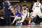 Memphis Grizzlies guard Ja Morant, right, dribbles aways from Sacramento Kings guard De'Aaron Fox, left, during the first quarter of an NBA basketball game in Sacramento, Calif., Thursday, Feb. 20, 2020. (AP Photo/Rich Pedroncelli)