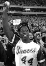 FILE - In this April 8, 1974, file photo, Atlanta Braves' Hank Aaron holds aloft the ball he hit for his 715th career home in Atlanta. Hank Aaron, who endured racist threats with stoic dignity during his pursuit of Babe Ruth but went on to break the career home run record in the pre-steroids era, died early Friday, Jan. 22, 2021. He was 86. The Atlanta Braves said Aaron died peacefully in his sleep. No cause of death was given. (AP Photo, File)