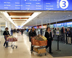 Frontier Airline employees move food and supplies in carts for TSA workers to a distribution center at Orlando International Airport as the partial government shutdown moves through its fourth week Wednesday, Jan. 16, 2019, in Orlando, Fla. (AP Photo/John Raoux)