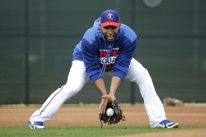 Texas Rangers shortstop Elvis Andrus fields a ball during spring training baseball practice Monday, Feb. 18, 2019, in Surprise, Ariz. (AP Photo/Charlie Riedel)