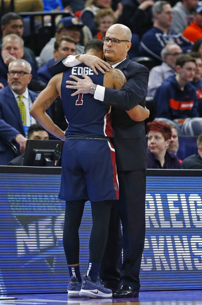 Fairleigh Dickinson coach Greg Herenda hugs Darnell Edge as Edge leaves in the second half against Gonzaga during a first-round game in the NCAA men's college basketball tournament Thursday, March 21, 2019, in Salt Lake City. (AP Photo/Rick Bowmer)